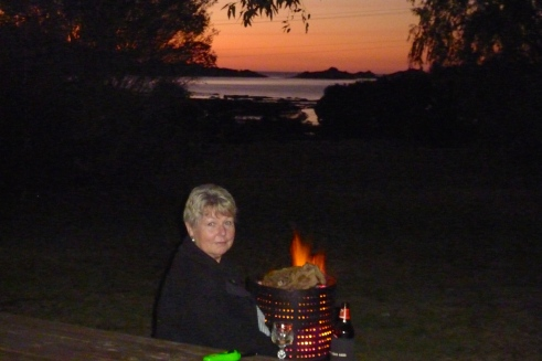 Having a drink in front of the fire as the sun sinks over Moonlight Bay.