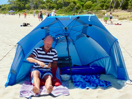 Paul putting on sun screen under our own beach shelter.